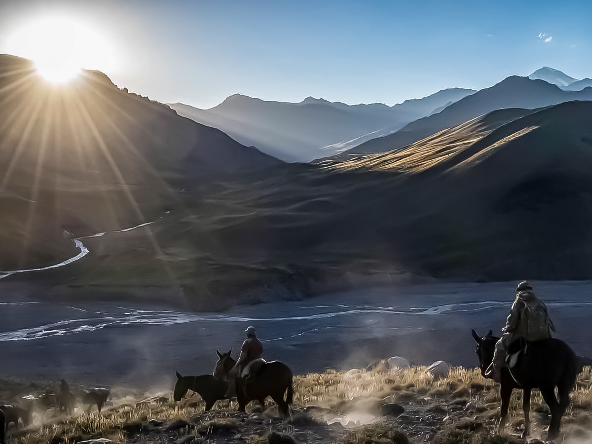 Horseback riding through the Andes in Argentina at sunset