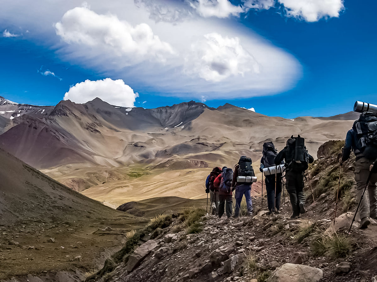 Trekking tour team walking through the Argentinian Andes mountain range