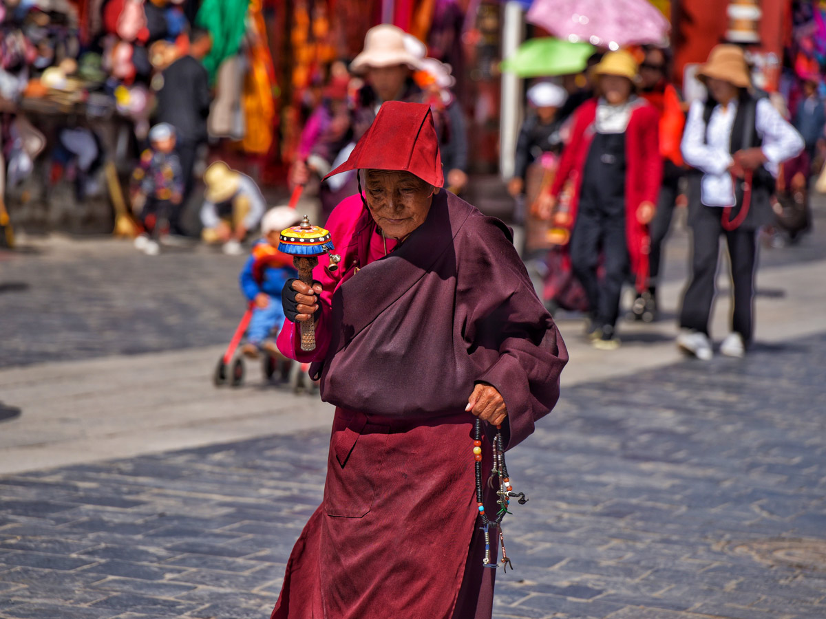 Old woman in ceremony on Barkhor Street seen niking in Tibet