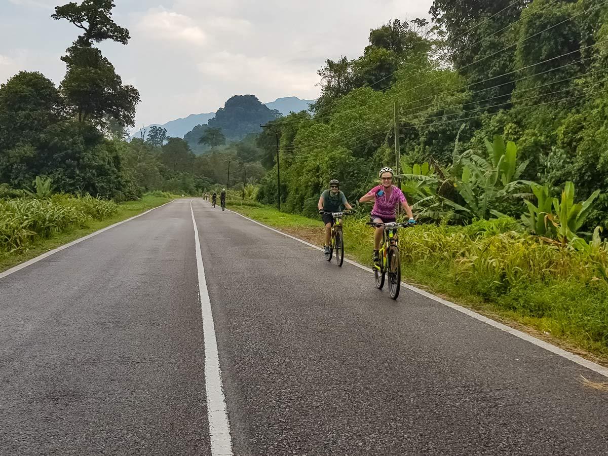 Cyclists road bike along Sarawak Rainforest Adventure tour in Malaysia