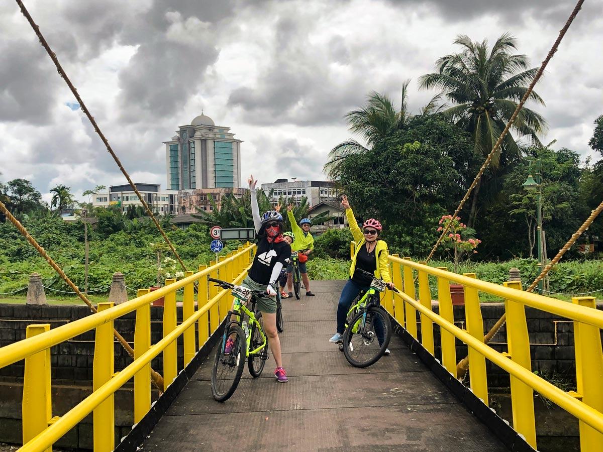 Cyclists pose on yellow bridge along Malasia Headhunters Heartland bike tour