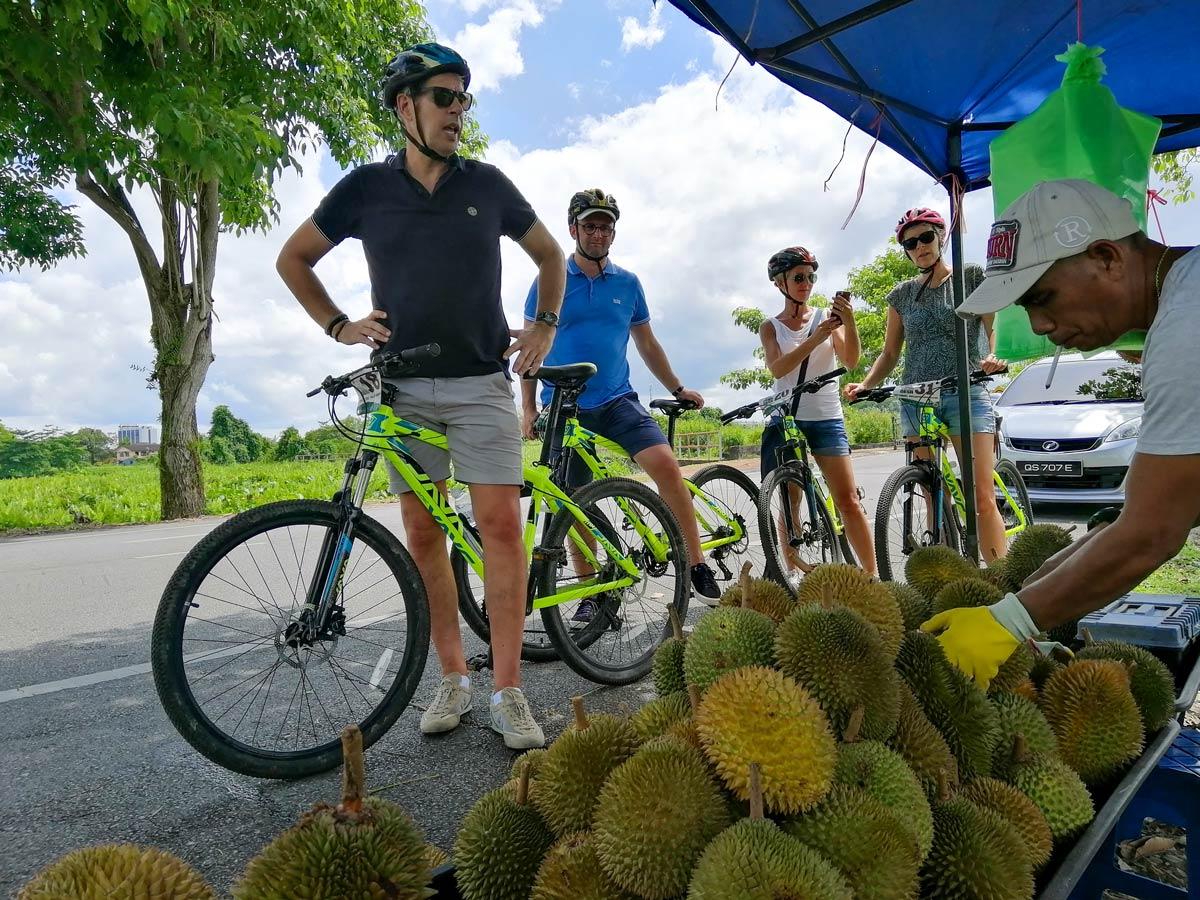 Cyclists stop at fruit stand along Malasia Headhunters Heartland bike tour