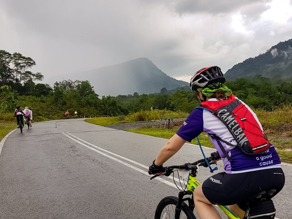 Bikers cycling through misty rainforest in Malaysia