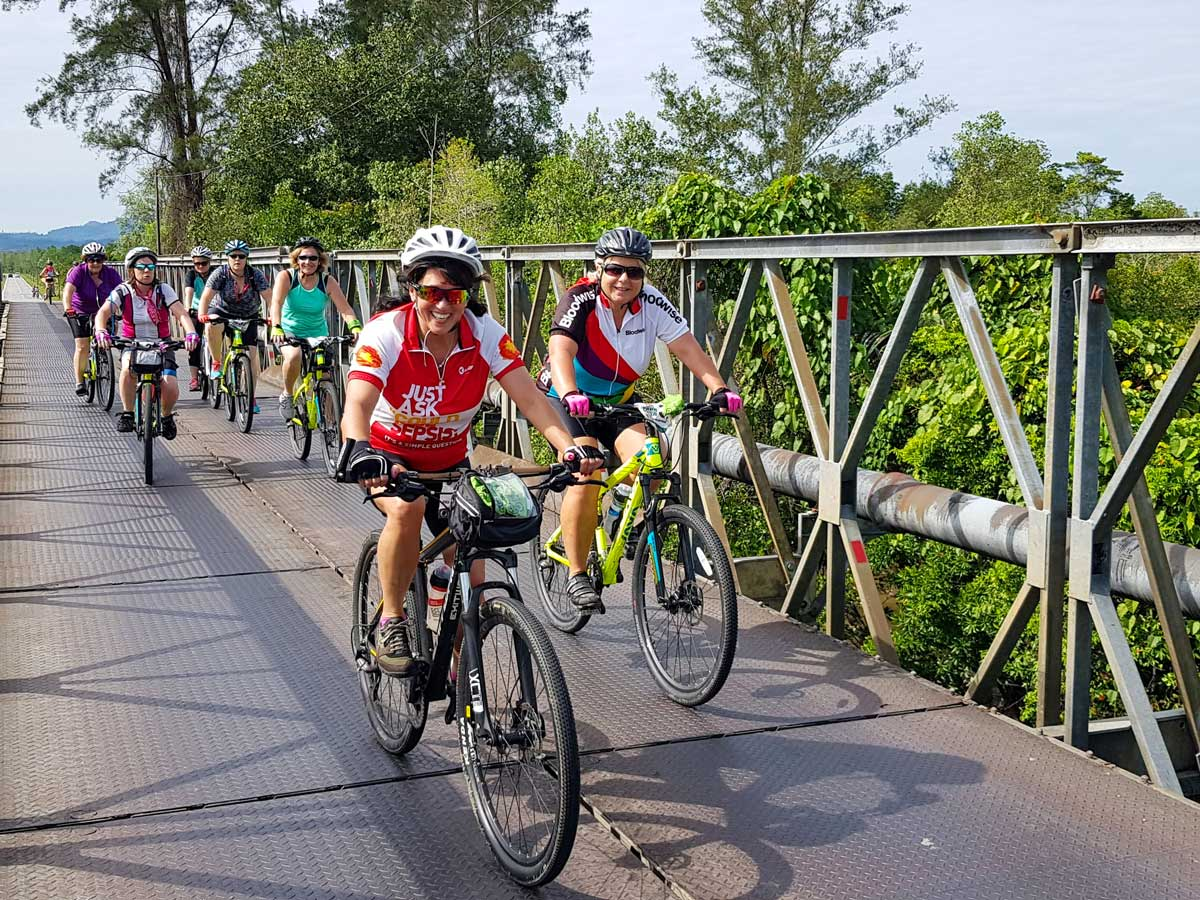 Cyclists biking along Malaysian rainforest ride