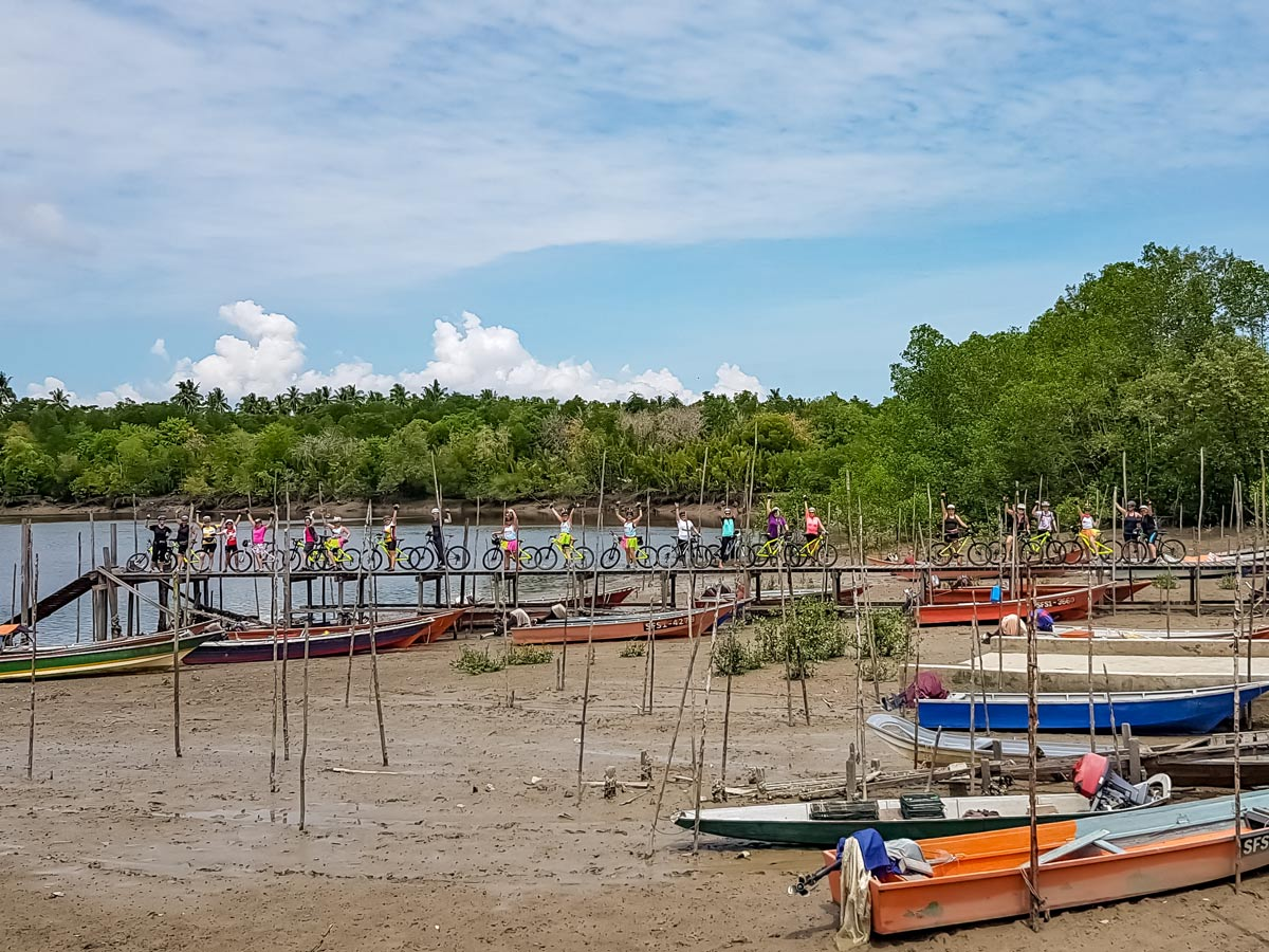 Cyclists on boat dock along Malaysian rainforest ride