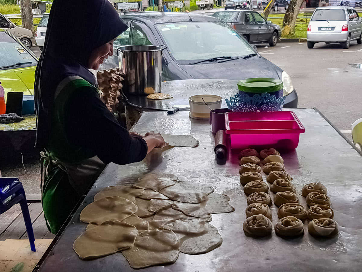Local woman making pastries along Trans Borneo road bike tour Malaysia