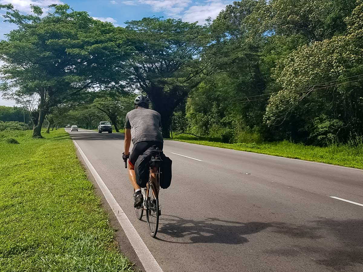 Cyclist road biking along Trans Borneo bike tour Malaysia