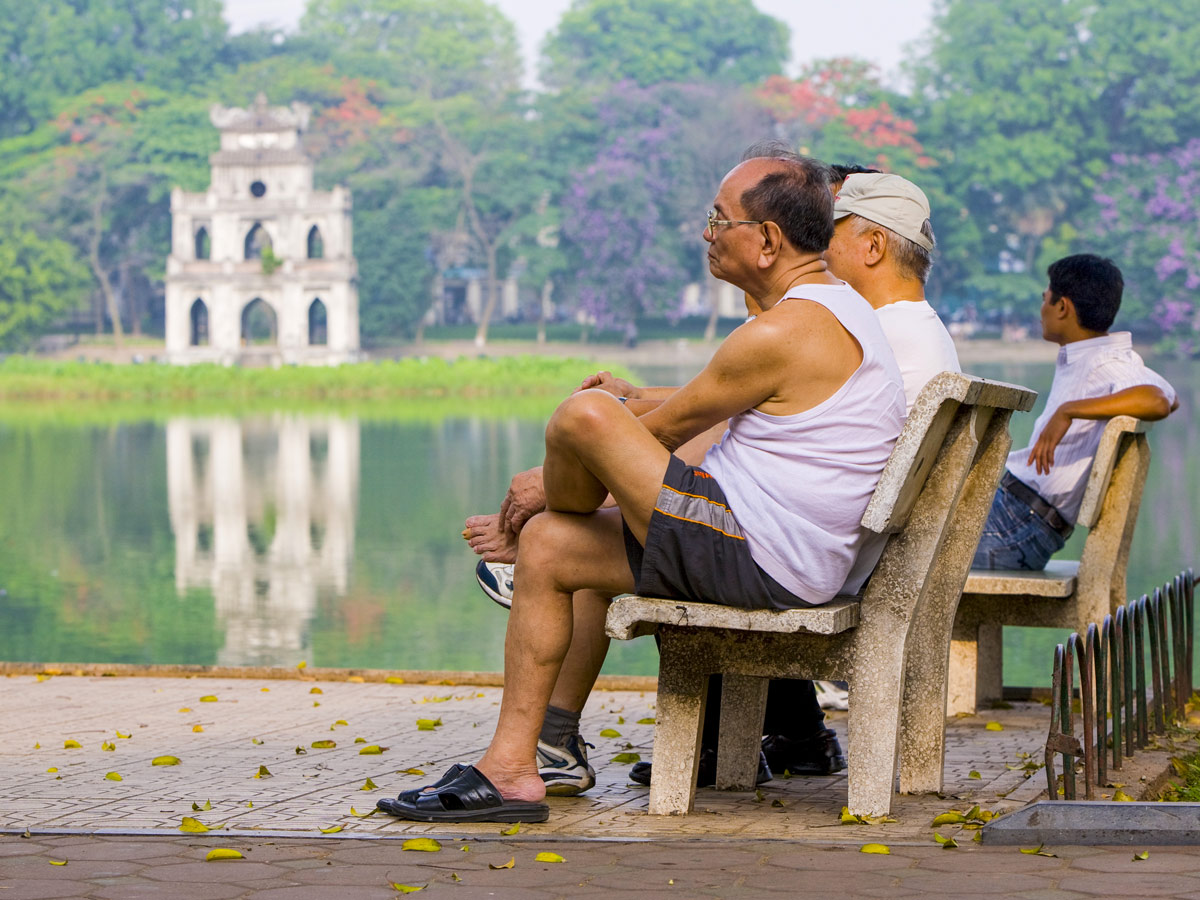 Old men rest by Hoan Kiem Lake seen on 2nd day of Red River Delta biking tour