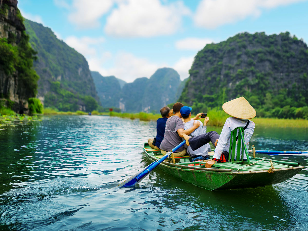 Tourists traveling in boat along the Ngo Dong River near Tam Coc Ninh Binh Vietnam