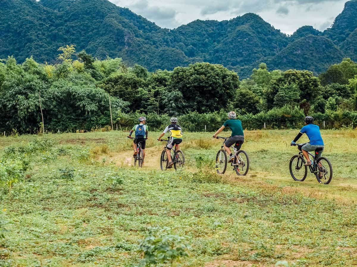 Cyclists crossing the field in Vietnam on guided tour