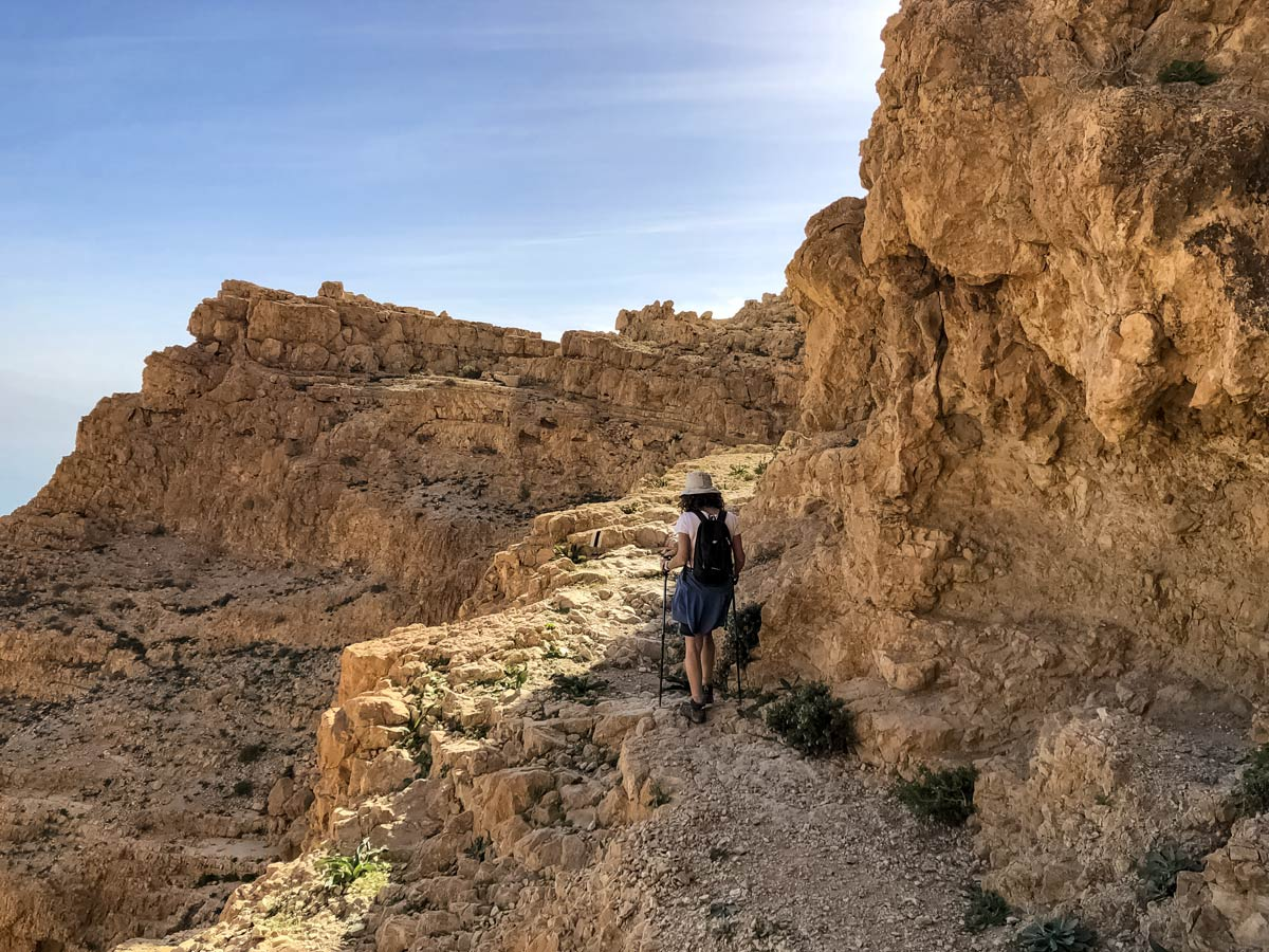 Hiker traverses rock cliff path hiking near Dead Sea in Israel trekking
