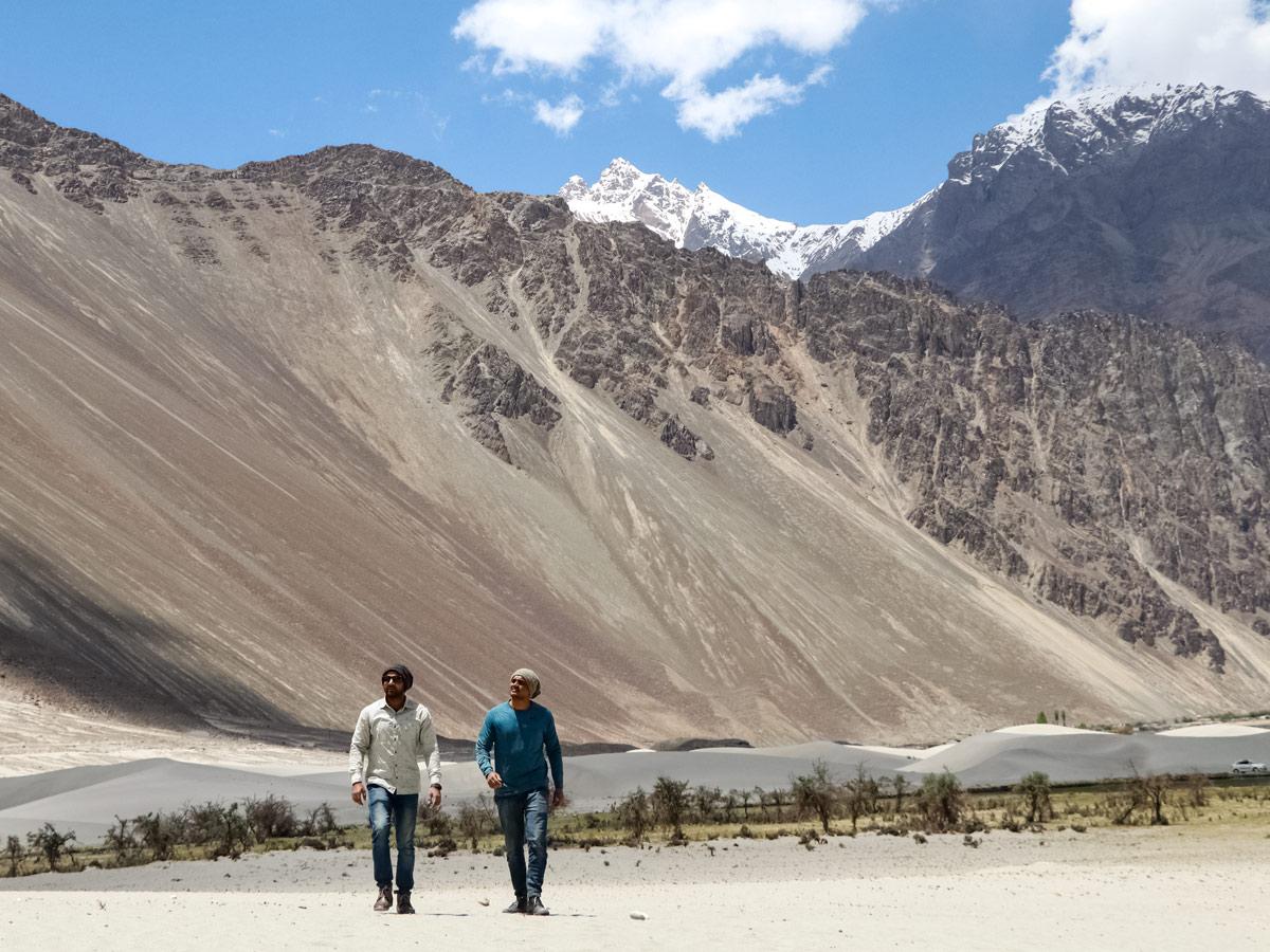 Two local men walk through Nubra Valley hiking in India