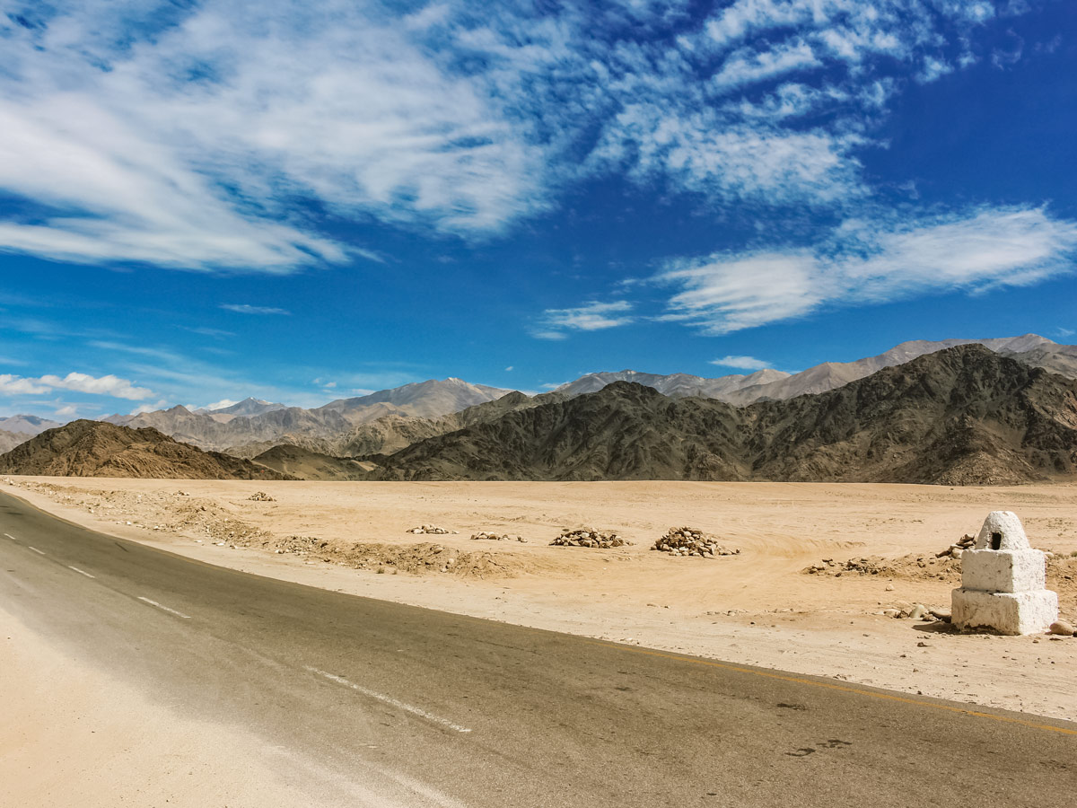 Sand drifts onto the highway in desert landscape Parang La India