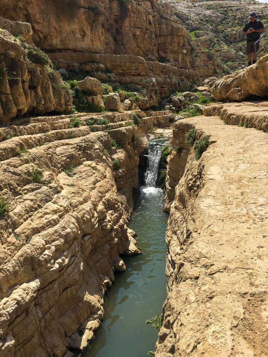 Hiker standing above waterfalls hiking Jericho to Jerusalem Israel