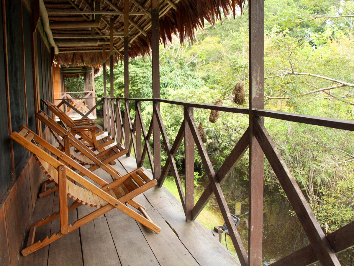 Amazon jungle wooden chairs relaxing on deck camping expedition Peru