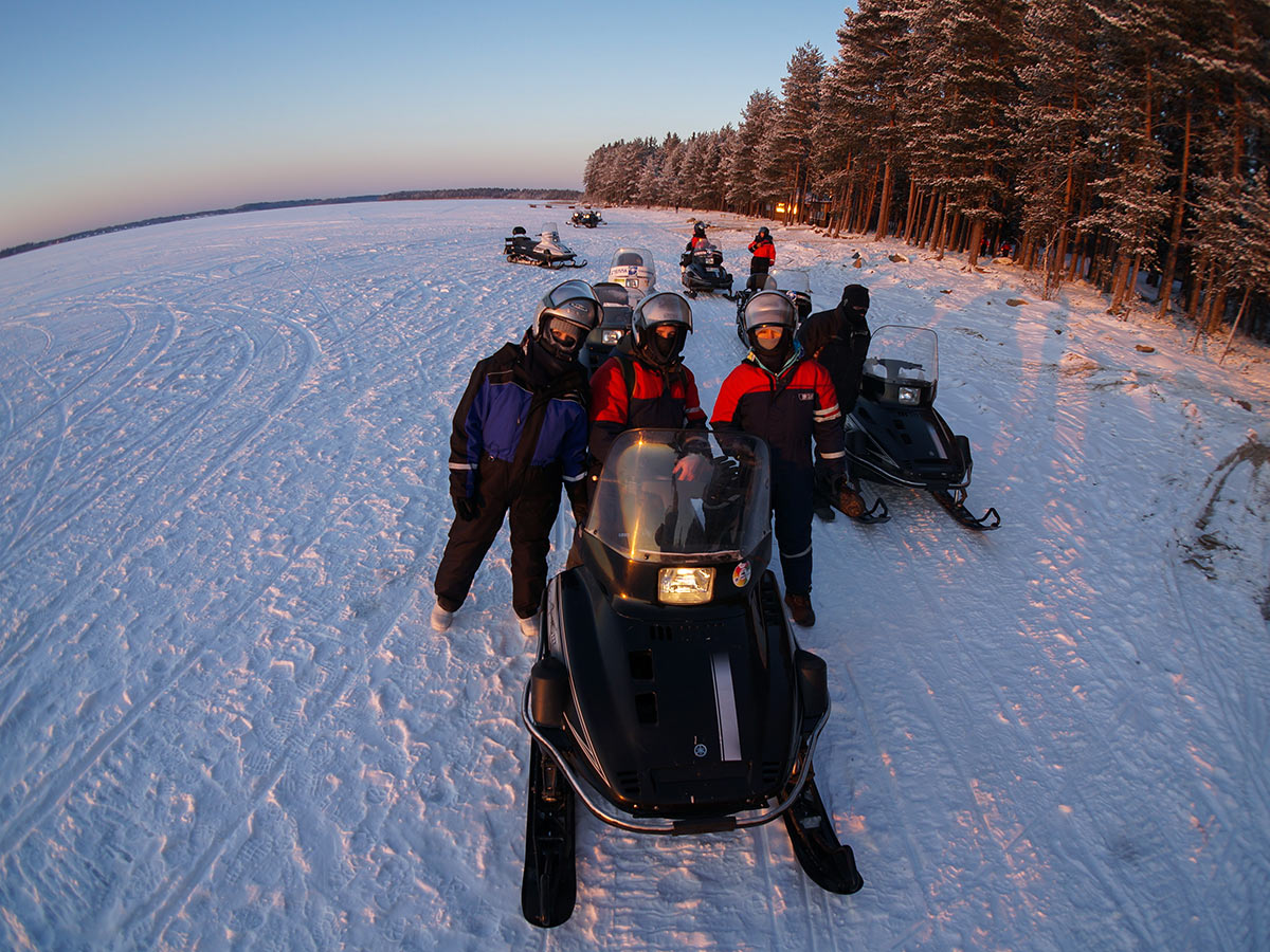 Riding snowmobiles on Karelia multi sport tour with a guide