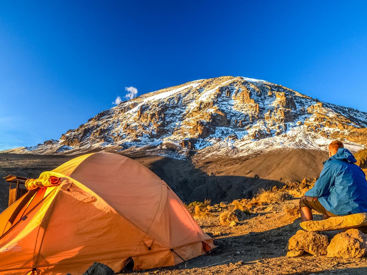 Hiker camping at Mount Kilimanjaro basecamp along trekking tour Tanzania