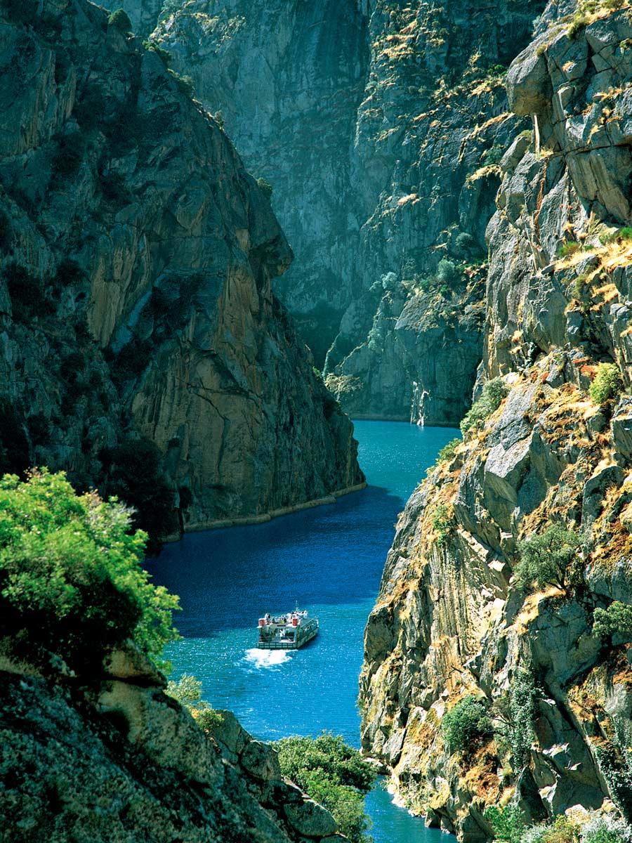 Boat ship in gorge fjord between rock cliffs