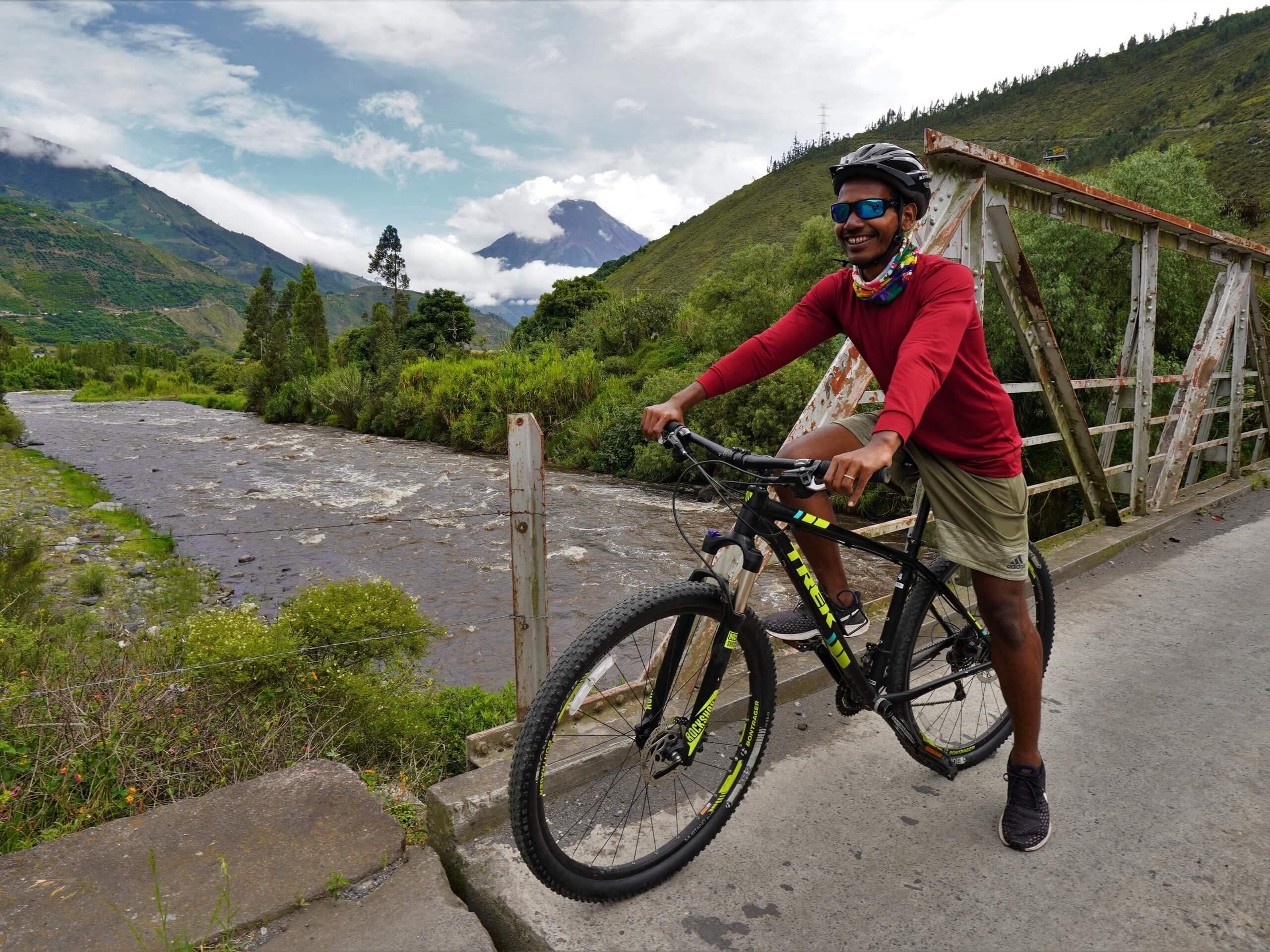 Biker crossing the bridge over the river near Banos