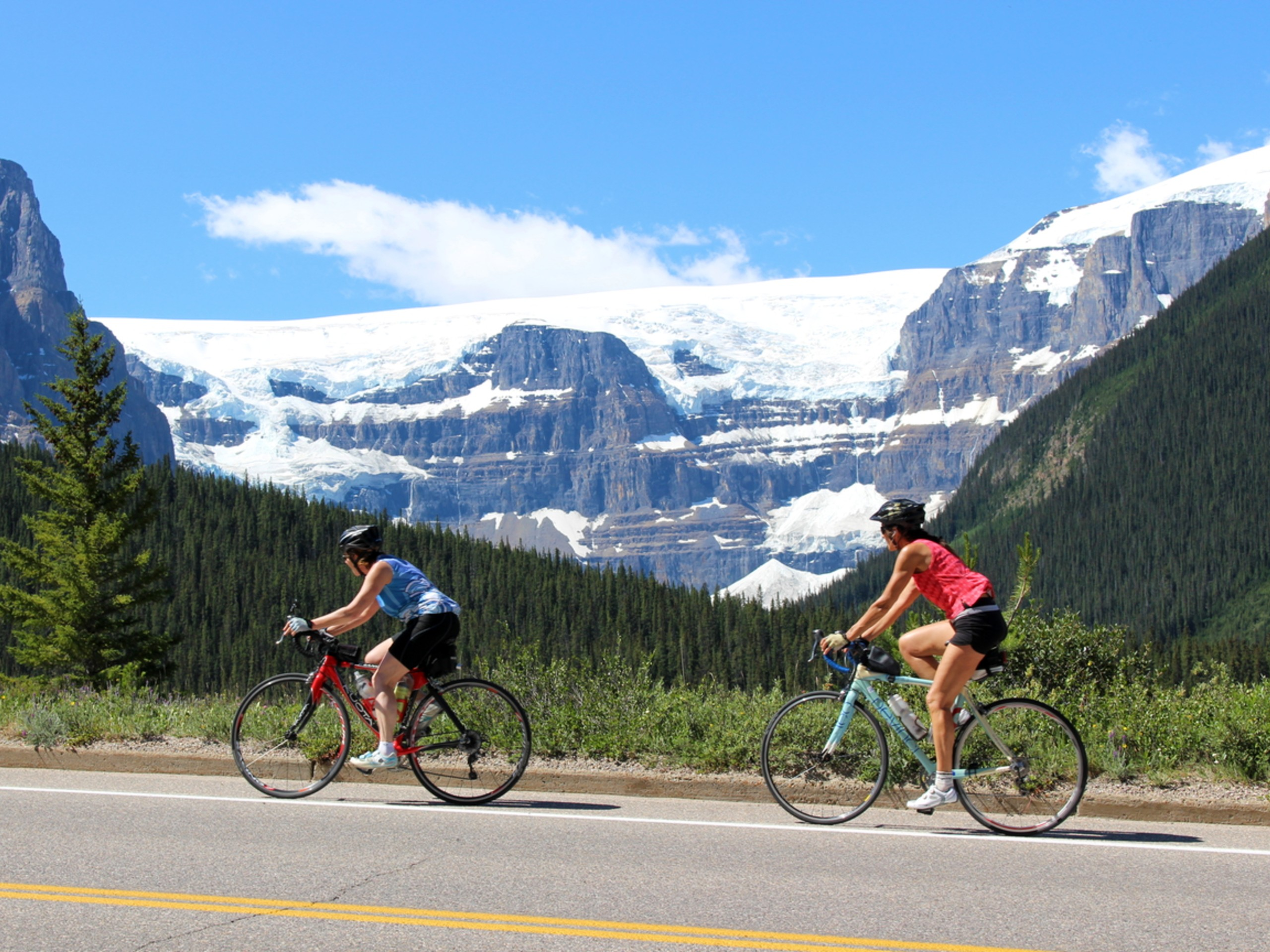 Two bikers riding the Icefields Parkway, in front of stunning glaciers