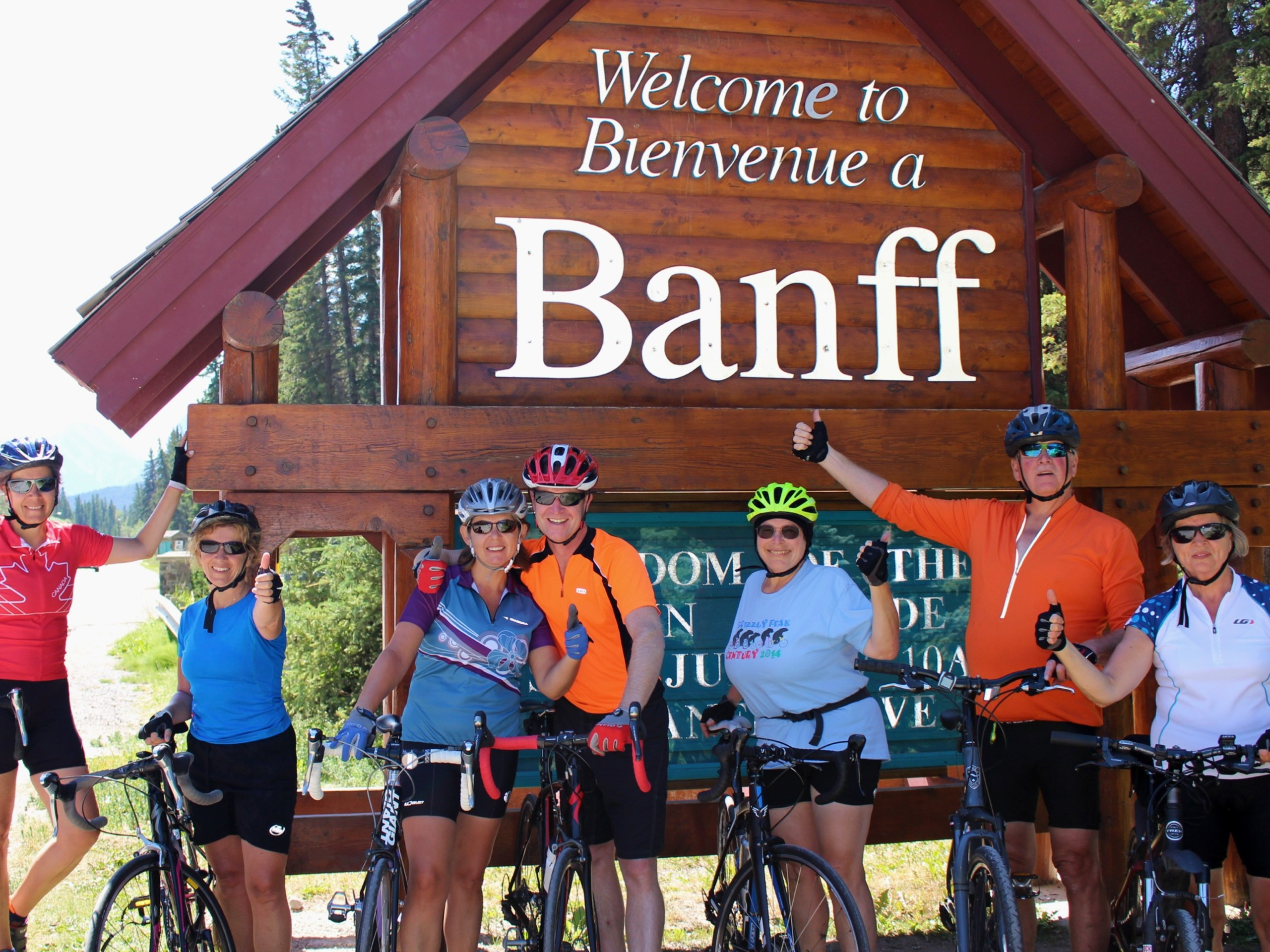 Cyclists posing near the entry sing to Banff