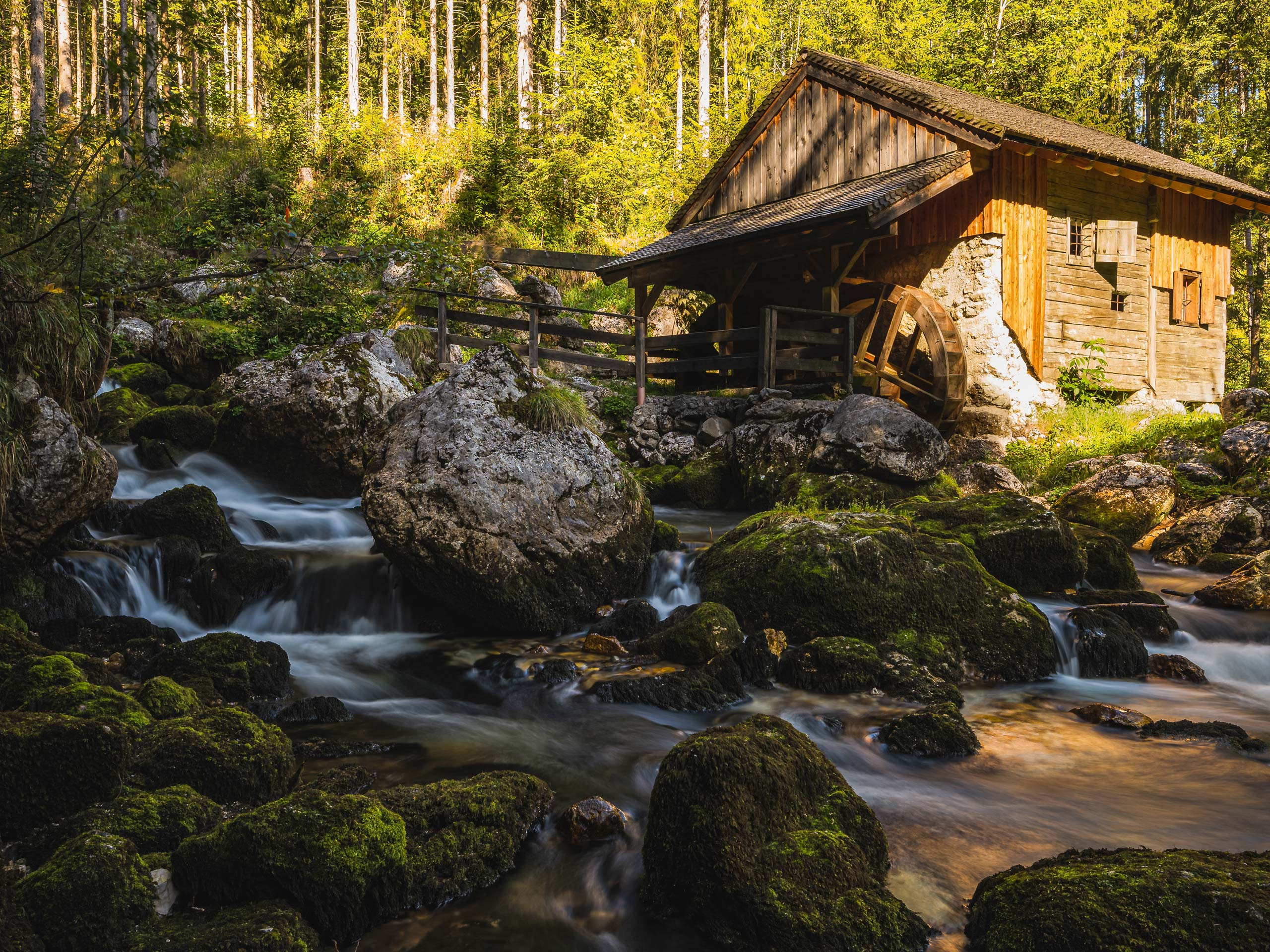 Golling waterfalls tumbling down rocks beside hut in Austria