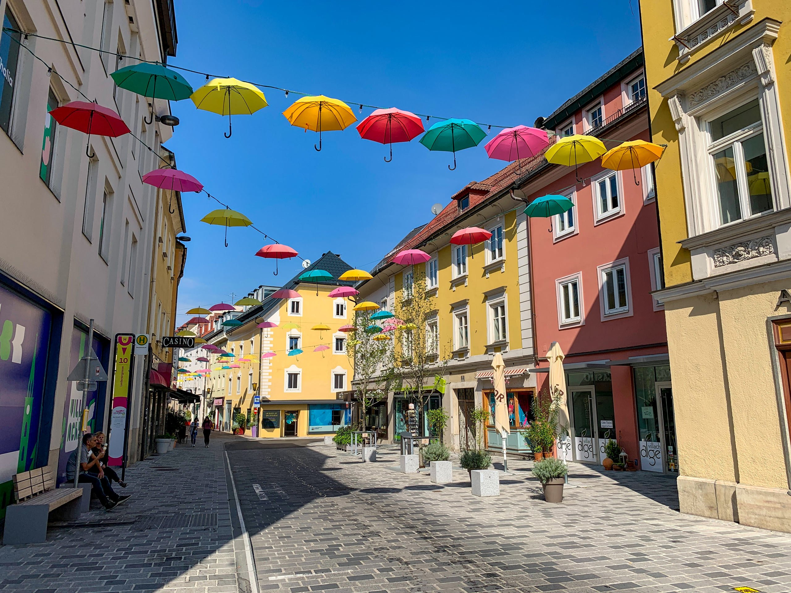 Colourful umbrellas hung over cobblestone street Villach town in Austria