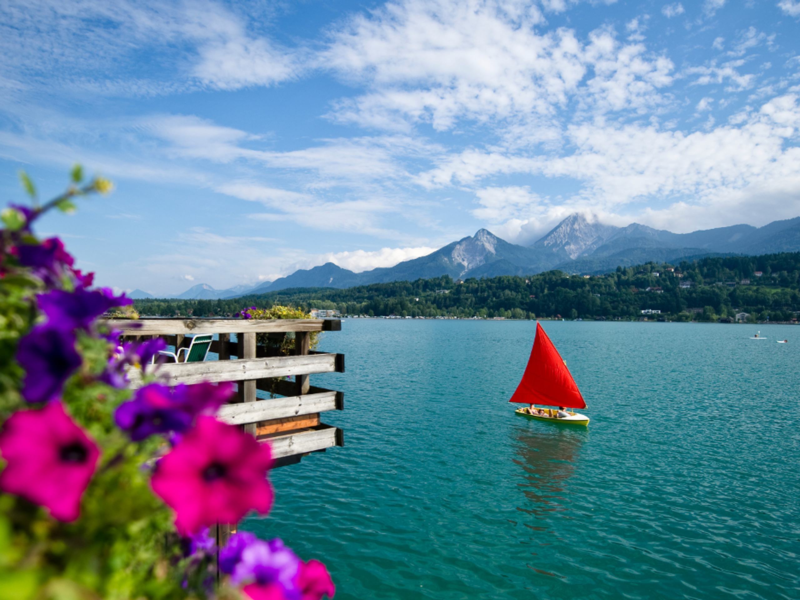 Boat with a red sail on the Lake Worthersee