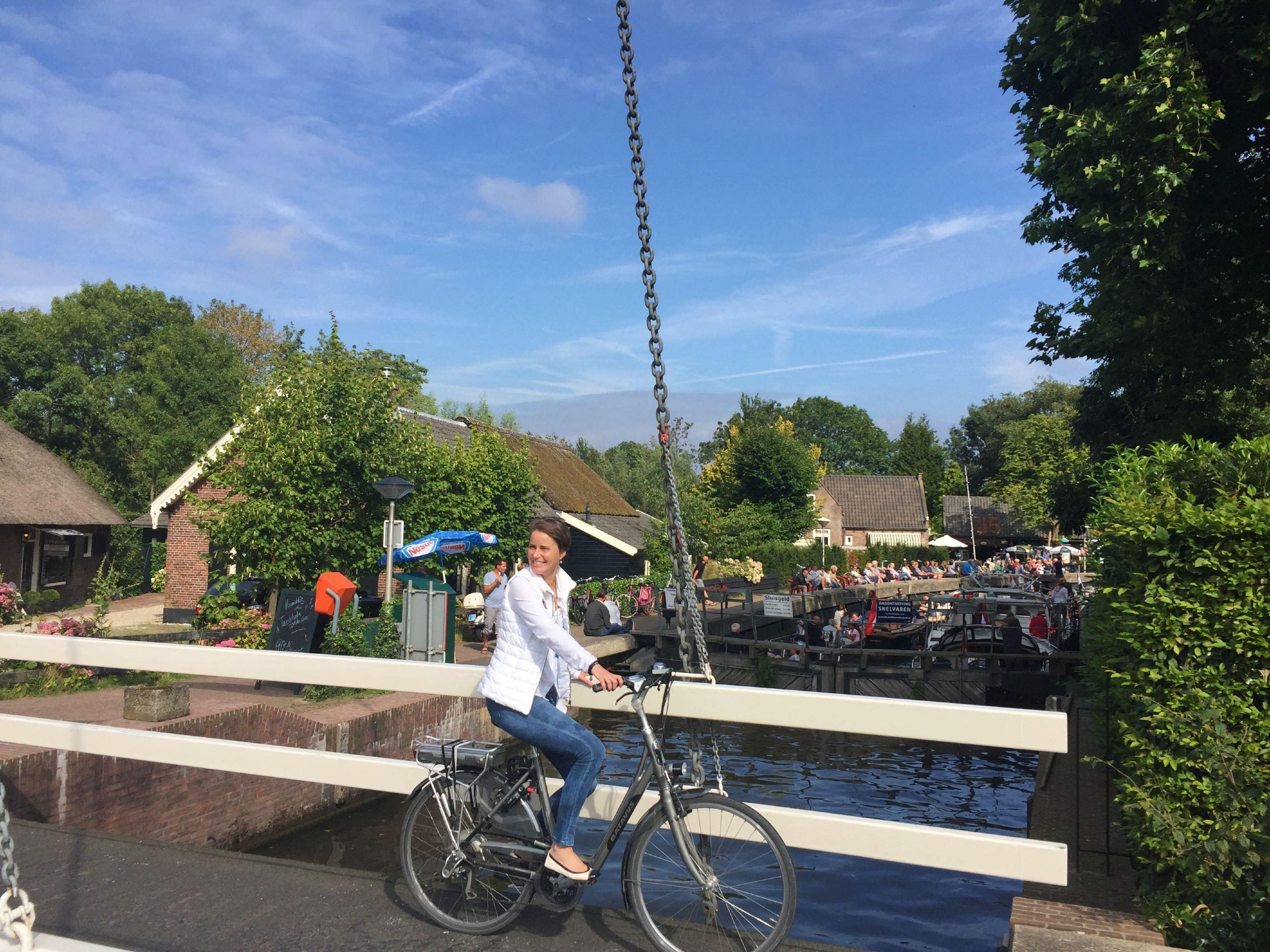Lady crossing the bridge on a bike in Vecht