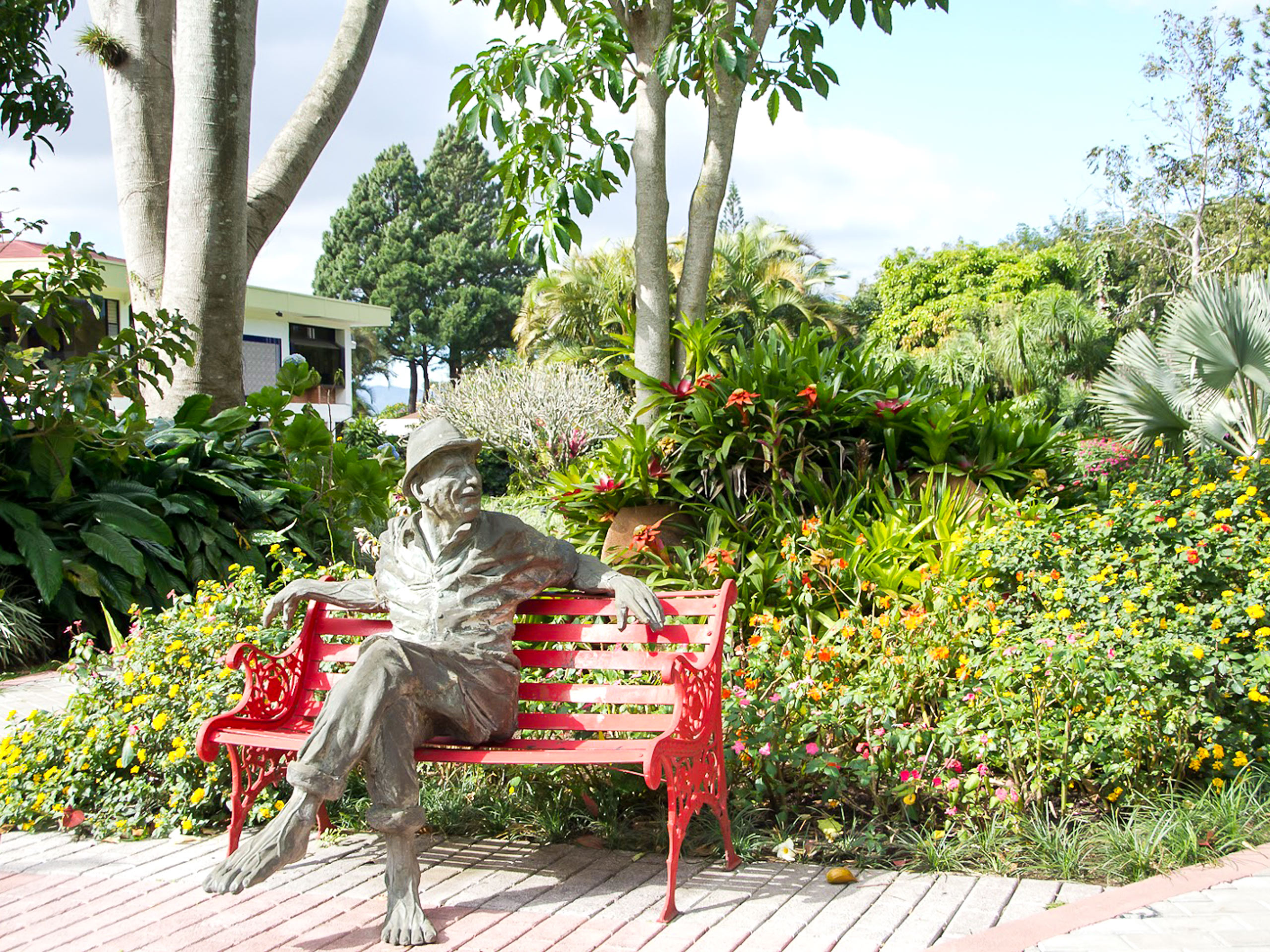 Bougainvillea Hotel garden statue on a bench