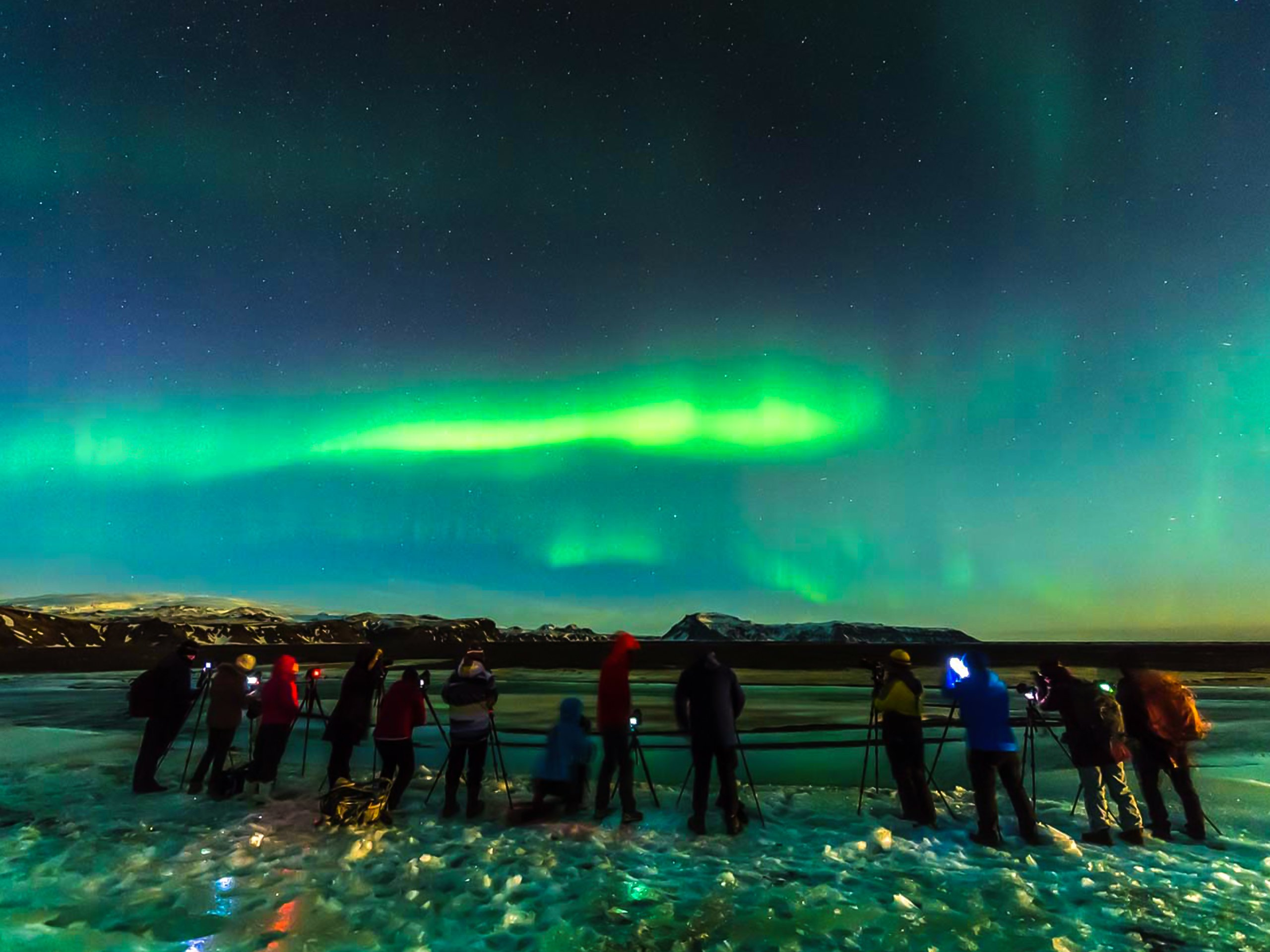 Group of Tourists Watching the Northern Lights